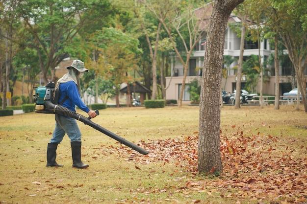 Jesienne liście czyszczenia przez pracownika z dmuchawy maszyny