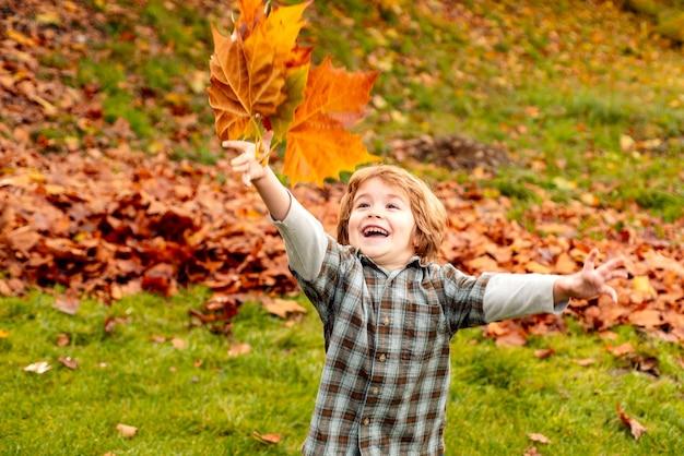 Jesienne liście dzieciak jesienny portret na zewnątrz słodkiego szczęśliwego chłopca spacerującego w parku lub lesie w ciepłym ...