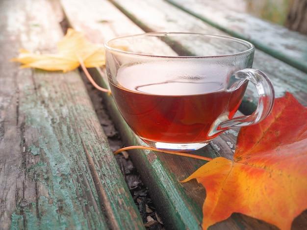 Jesienne liście i gorąca filiżanka herbaty. drewniany stół przeciw pogodnemu zimnemu dniu na naturalnym tle.