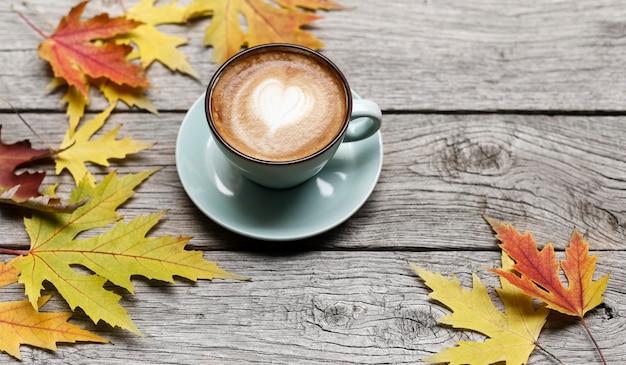 Jesienne liście i kompozycja cappuccino. niebieska filiżanka z pianką, przy wyblakłym rustykalnym drewnianym stole. upadek koncepcji gorących napojów