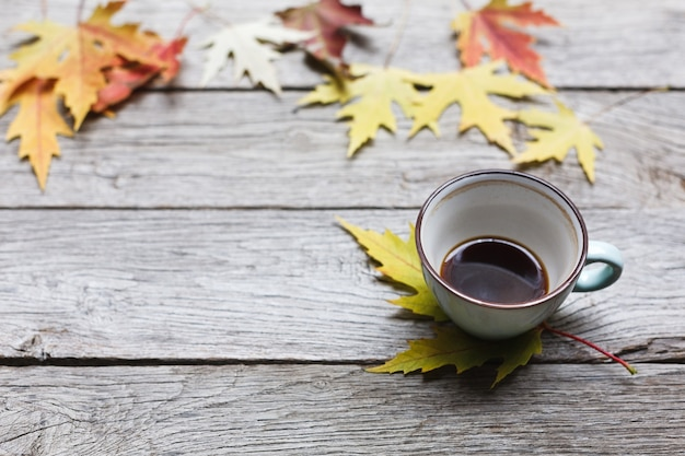 Jesienne liście i kompozycja czarnej kawy. niebieski kubek do kawy w połowie pusty na wyblakły rustykalny drewniany stół. upadek koncepcji gorących napojów
