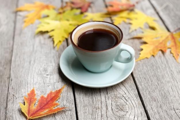 Jesienne liście i kompozycja espresso. niebieski kubek czarnej kawy, przy wyblakłym rustykalnym drewnianym stole. upadek koncepcji gorących napojów