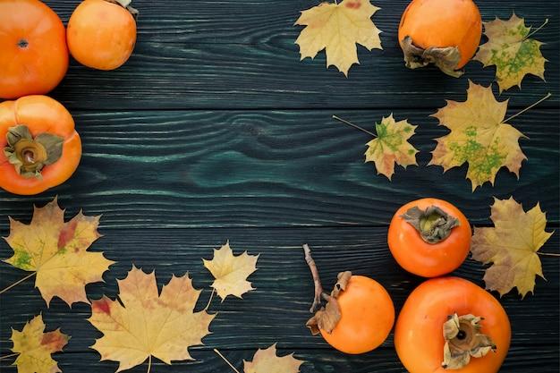 Jesienne liście klonu i dojrzałe persimmons na teksturowanej drewniane tła