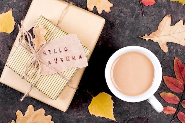 Jesienne liście klonu i filiżanka czarnej kawy - karta jesień do projektowania, widok z góry