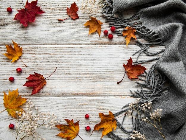 Jesienne liście klonu i wełniany szalik na tle drewnianych. jesienne tło.