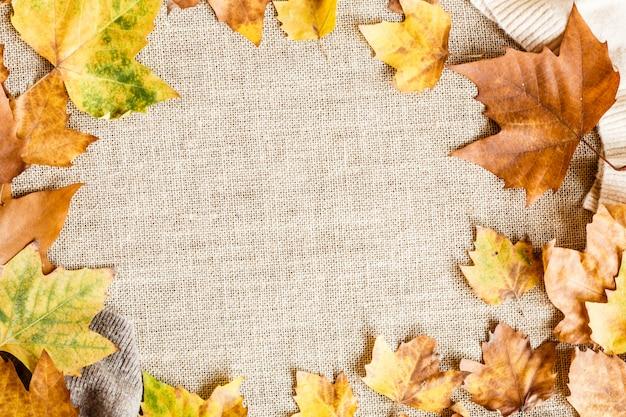 Jesienne liście klonu na brązowym tle.