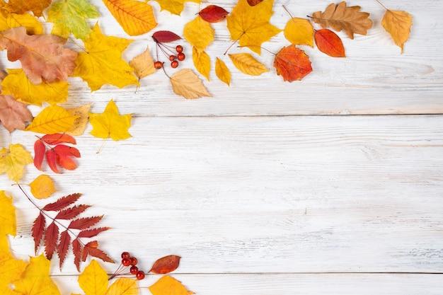 Jesienne liście klonu na drewnianym stole. spadające liście naturalne tło.