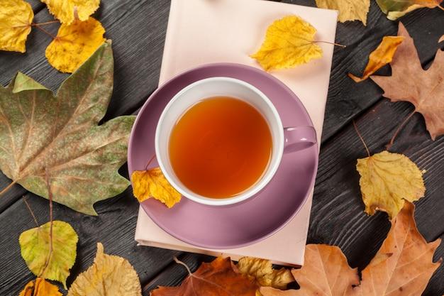 Jesienne liście, książka i filiżanka herbaty