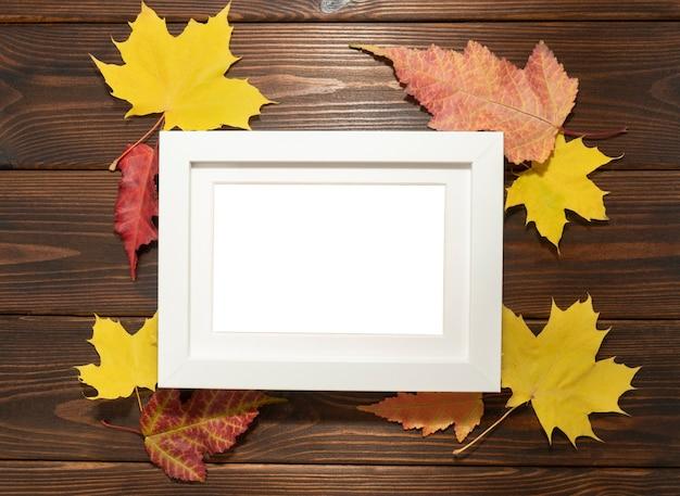 Jesienne liście na drewnianym tle, jesienna ramka liściowa pusta ramka na zdjęcia, kopia przestrzeń