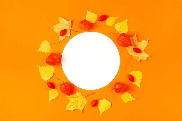 Jesienne liście na pomarańczowej powierzchni