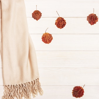 Jesienne liście osikowego drzewa w pobliżu przytulnego szalika tekstylnego