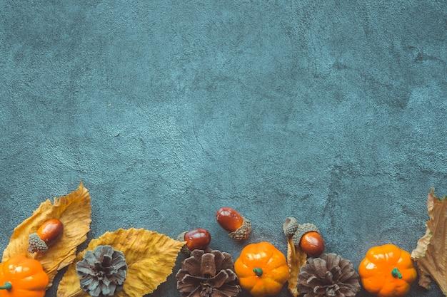 Jesienne liście, ozdobne dynie, żołędzie i szyszki na niebieskim tle drewnianych