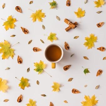 Jesienne liście wzór z filiżanką kawy lub herbaty na białej ścianie. leżał na płasko.