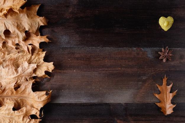 Jesienne liście z sercem i anyżem na drewnianym stole