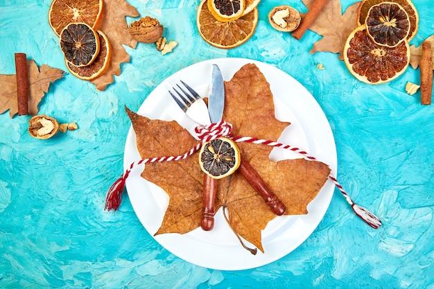 Jesienne lub jesienne nakrycie stołu ozdobione jesiennymi liśćmi.