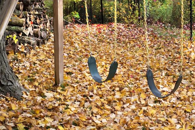 Jesienne lub jesienne podwórko pełne liści i huśtawki.