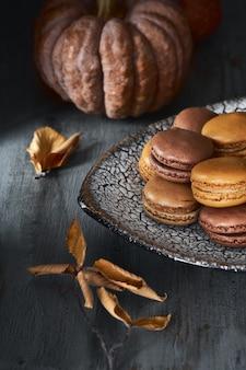 Jesienne macarons z karmelem i kakao z kawą na ciemnym rustykalnym drewnie