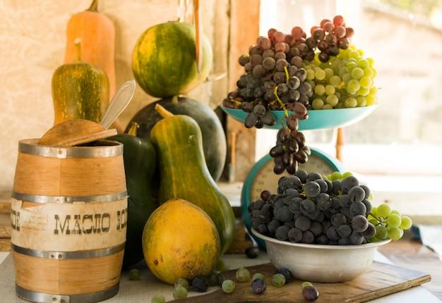 Jesienne martwa natura z dyniami, melonami, arbuzem, winogronami na skalę iw metalowej misce na drewnianym białym stole. koncepcja zbiorów jesienią. szczęśliwego święta dziękczynienia. selektywne ustawianie ostrości. szablon projektu.
