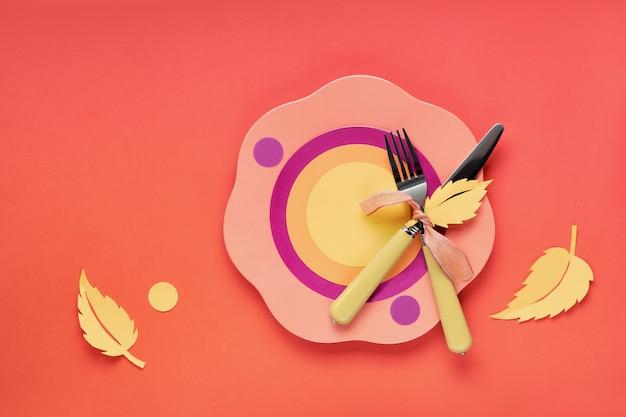 Jesienne mieszkanie koncepcyjne leżało w odważnych kolorach z talerzem, widelcem, nożem i dekoracyjnymi jesiennymi liśćmi w kolorach żółtym, pomarańczowym, czerwonym i fioletowym. minimalistyczna koncepcja menu sezonowego.