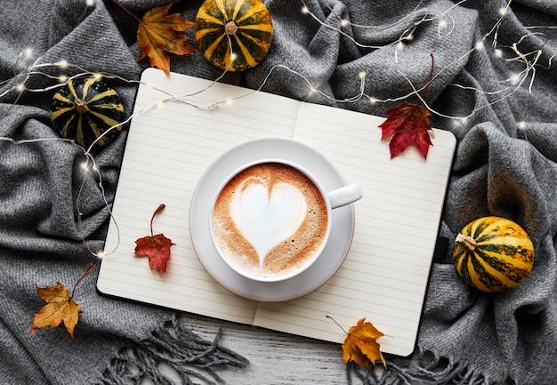 Jesienne mieszkanie leżało z filiżanką kawy, liśćmi, pompką i ciepłym kocem