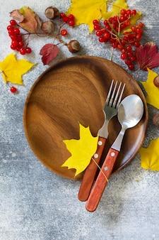 Jesienne nakrycie stołu święto dziękczynienia lub jesienne nakrycie stołu z rustykalnymi sztućcami