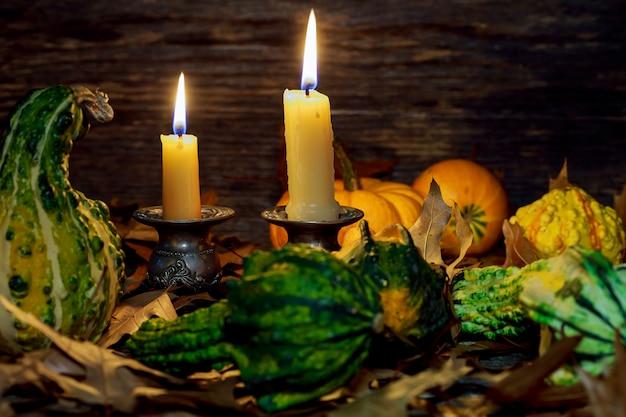 Jesienne nakrycie stołu z dyniami i świecami, dekoracja domu na święta