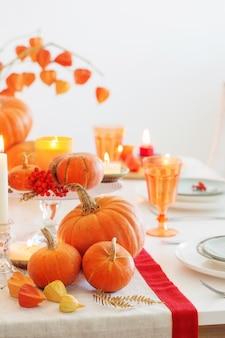 Jesienne nakrycie stołu z płonącymi świecami i dyniami