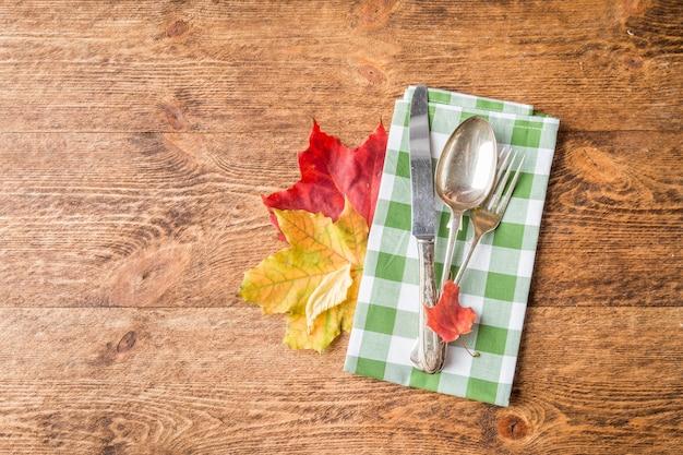 Jesienne nakrycie stołu ze sztućcami i ułożeniem jesiennych liści