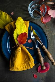 Jesienne nakrycie z żółtymi i czerwonymi liśćmi na rustykalnym tle z miejsca na kopię