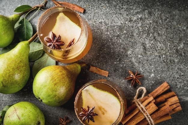 Jesienne napoje. grzane wino. tradycyjny jesienny pikantny koktajl z gruszką, cydrem i syropem czekoladowym