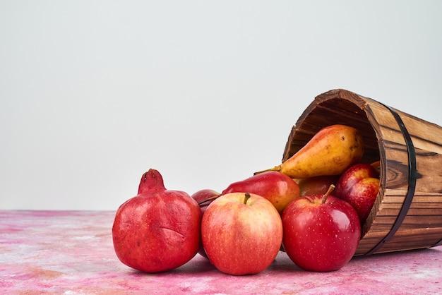 Jesienne owoce na drewnianym wiadrze.