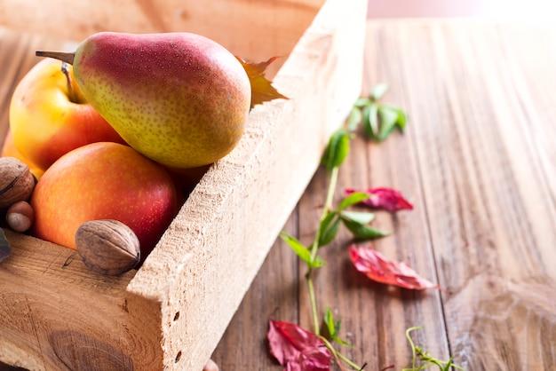 Jesienne owoce w drewnianym pudełku