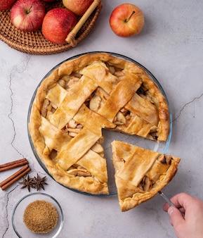 Jesienne potrawy. widok z góry na domową szarlotkę na białym drewnianym stole, ręka biorąca kawałek ciasta