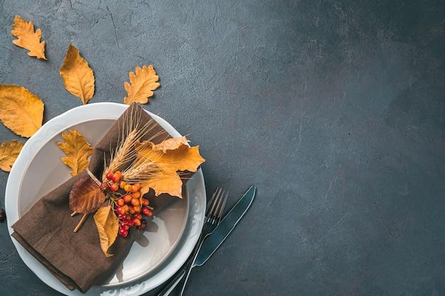 Jesienne świąteczne tło z talerzami serwującymi jagody na serwetce i jesienne liście na ciemnym tle