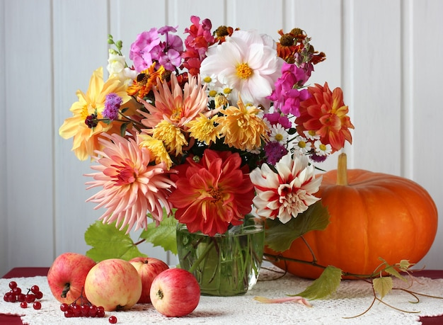 Jesienne światło martwa natura z bukietem kwiatów, jabłek i dyni na stole. żniwa, obfitość.