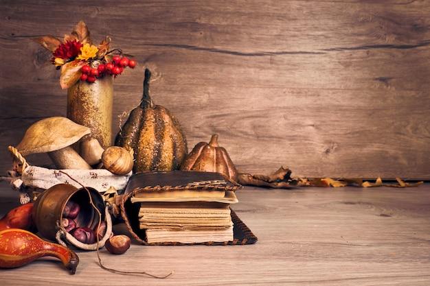 Jesienne święto dziękczynienia z drewnianymi grzybami, dekoracyjnymi dyniami, jesiennymi liśćmi, jabłkami, papryką i kasztanami. jesienne martwa aranżacja wnętrz, stare antyczne książki na starym drewnianym stole.