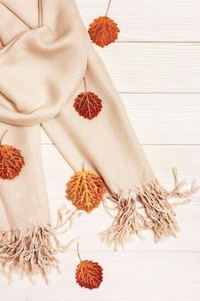 Jesienne tło, białe drewno z suchą czerwoną porą jesiennych liści osiki, przytulny szalik tekstylny. skopiuj miejsce widok z góry.