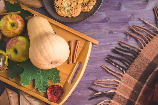 Jesienne tło. ciastka, dyniowi liść szkockiej kraty jabłka na drewnianym tle
