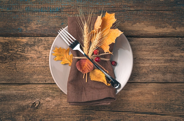 Jesienne tło kulinarne talerz z lnianą serwetką, widelec i jesienne liście