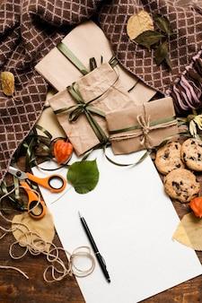 Jesienne tło przygotowania prezentów. widok z góry małych zapakowanych prezentów z czekoladowymi ciasteczkami, nożyczkami i opaskami, czysty papier z długopisem leżącym na drewnianym stole w kratę
