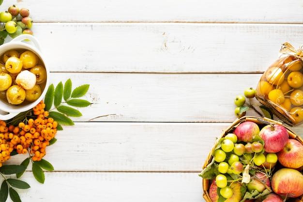 Jesienne tło... raj jabłka w syropie cukrowym na białym drewnianym stole. zbiór jesiennych zbiorów. rajski dżem jabłkowy. widok z góry. skopiuj miejsce.