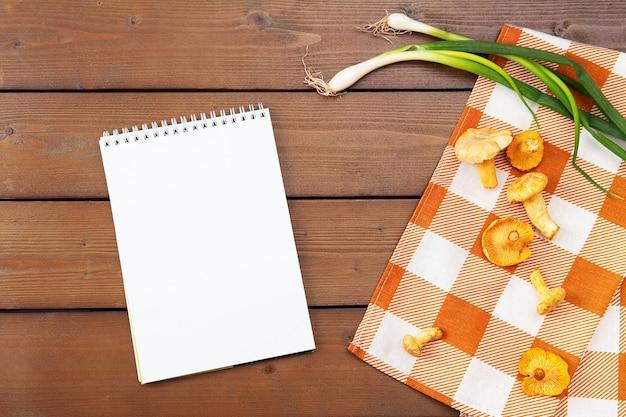 Jesienne tło. surowe kurki złote, grzyby sezonowe, zbiory na drewnianym stole z serwetką w kratkę i zieloną cebulką. pusta biała kartka notebooka, miejsce na tekst, miejsce.