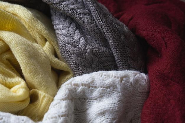 Jesienne tło w ciepłych kolorach z różnymi wełnianymi dzianinowymi swetrami lub pledami.