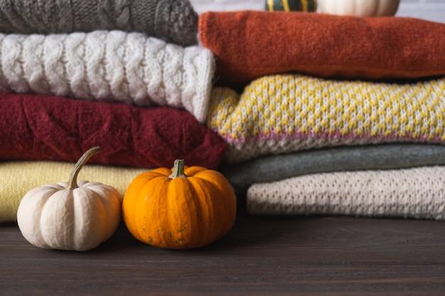 Jesienne tło w ciepłych kolorach z różnymi wełnianymi swetrami i dyniami