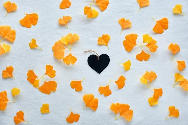 Jesienne tło w kolorze pomarańczowym i brązowym. jedwabny pomarańczowy miłorząb pozostawia na białym tle włókienniczych. w środku czarne drewniane serce.