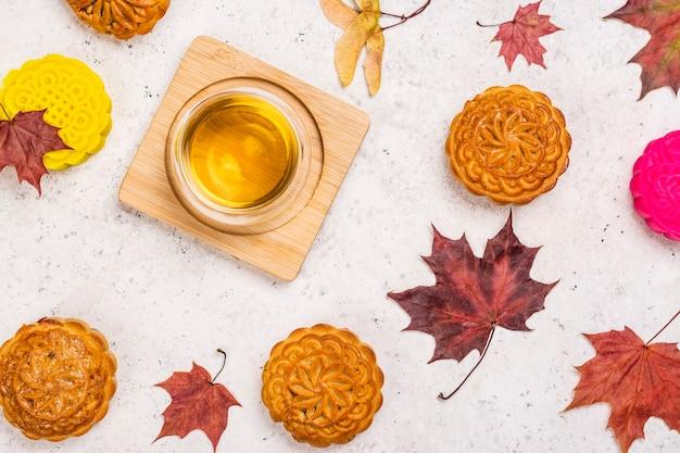 Jesienne tło z tradycyjnymi chińskimi ciastami księżycowymi i jesiennymi liśćmi klonu. karta z pozdrowieniami festiwalu połowy jesieni. skopiuj miejsce