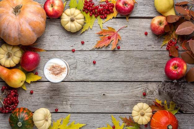 Jesienne tło z żółtymi liśćmi klonu, czerwonymi jabłkami, dyniami i pikantną latte. rama jesiennych zbiorów na wieku drewna.