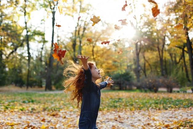 Jesienne wibracje, portret dziecka. urocze i czerwone włosy dziewczynki wygląda szczęśliwy chodzenia i gry na t