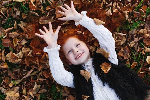 Jesienne wibracje, portret dziecka. urocze i czerwone włosy dziewczynki wygląda szczęśliwy leżącego na leżącym leav