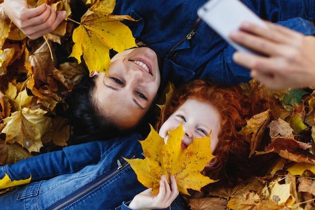 Jesienne wibracje, portret rodzinny. urocza mama i jej córeczka z rudymi włosami bawią się, biorąc selfie na sm